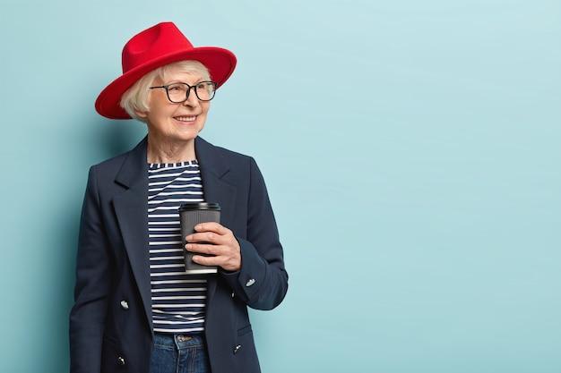 Aangenaam uitziende blije volwassen vrouw drukt positieve emoties uit, draagt een elegant jasje en een rode hoed, houdt een wegwerpbeker vast, drinkt warme drank, gefocust opzij, glimlacht breed