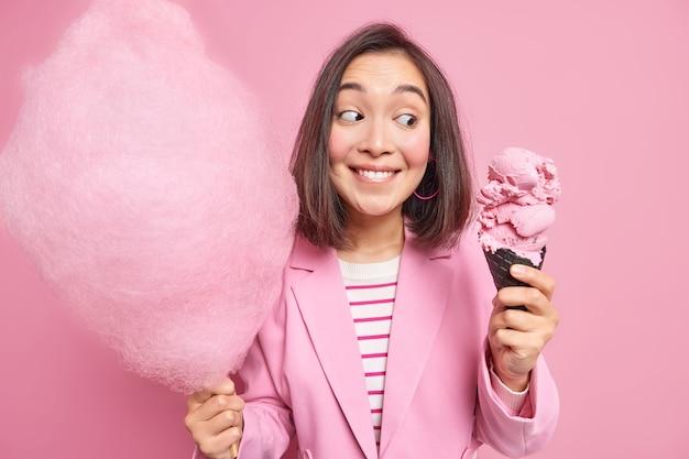 Aangenaam uitziende brunette aziatische vrouw kijkt naar smakelijk kegelijs houdt suikerspin op stokje geniet van zomerse desserts eet junkfood gekleed in roze jas poseert binnen heeft wandeling in park