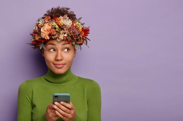 Aangenaam uitziende, doordachte herfstdame draagt natuurlijke krans, gebruikt mobiele telefoon om online te winkelen, gefocust opzij, geïsoleerd over paarse muur.