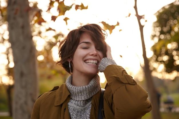 Aangenaam uitziende gelukkige jonge mooie brunette vrouw met opgeheven handpalm op haar hoofd en vrolijk lachend met gesloten ogen tijdens het lopen over vergeelde bomen bij zonsondergang
