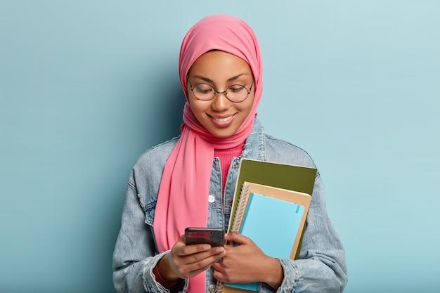 Aangenaam uitziende glimlachende vrouw gehuld in roze sluier, studeert aan de universiteit
