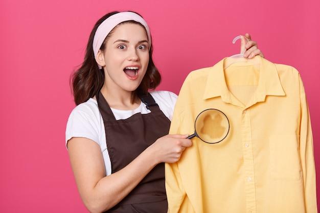 Aangenaam uitziende huisvrouw met verbaasde blik, draagt witte haarband, t-shirt en bruin schort, vrouw toont grote vlek met vergrootglas, moet onzuiverheden verwijderen.