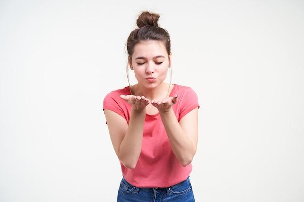 Aangenaam uitziende jonge aantrekkelijke bruinharige vrouw met knot kapsel handen opheffen naar haar gezicht en pruilende lippen met gesloten ogen, geïsoleerd op witte achtergrond