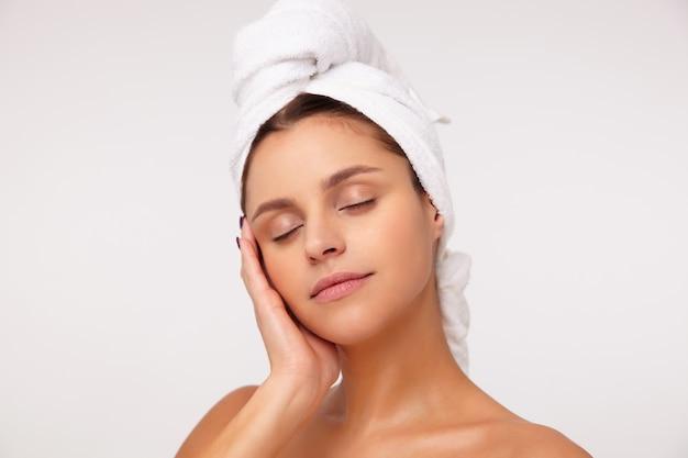 Aangenaam uitziende jonge aantrekkelijke brunette vrouw zonder make-up zachtjes haar gezicht aan te raken met opgeheven hand en de ogen gesloten te houden terwijl ze op een witte achtergrond met een handdoek op het hoofd staat