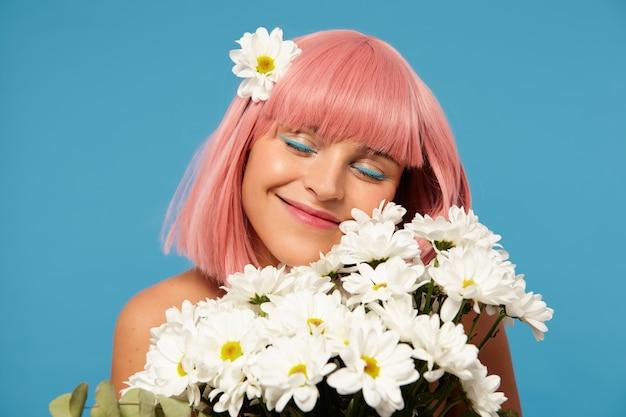 Aangenaam uitziende jonge aantrekkelijke dame met kort roze haar die haar witte perfecte tanden laat zien terwijl ze zachtjes glimlacht met gesloten ogen, staande over de blauwe achtergrond met een boeket bloemen