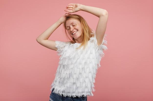 Aangenaam uitziende jonge aantrekkelijke roodharige dame die elegante kleding draagt terwijl ze over een roze achtergrond staat, vrolijk danst op muziek in haar oortelefoon en oprecht glimlacht
