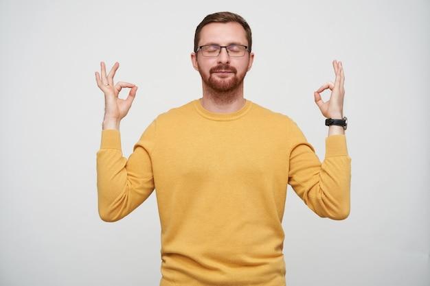 Aangenaam uitziende jonge brunette bebaarde man in brillen handen opheffen met mudra gebaar en ogen gesloten houden, mosterd trui dragen terwijl poseren