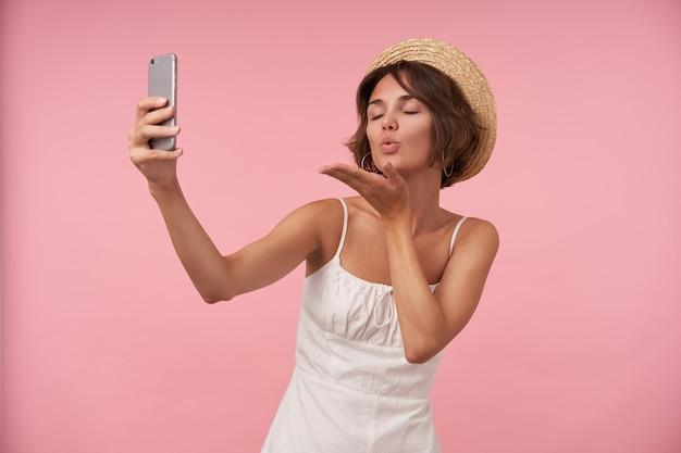 Aangenaam uitziende jonge brunette dame in strooien hoed en witte elegante jurk smartphone in opgeheven hand houden en blazen lucht kus met gesloten ogen, geïsoleerd