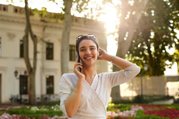 Aangenaam uitziende jonge brunette vrouw met zonnebril op haar hoofd met leuk gesprek aan de telefoon en gelukkig lachend, wandelen langs straat op zonnige dag