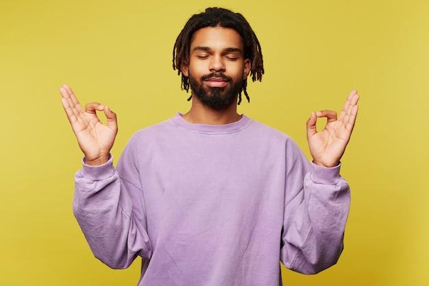 Aangenaam uitziende jonge donkere bebaarde man in paars sweatshirt die zijn oog gesloten houdt terwijl hij over de gele achtergrond staat en zijn handen opheft met mudra-gebaar