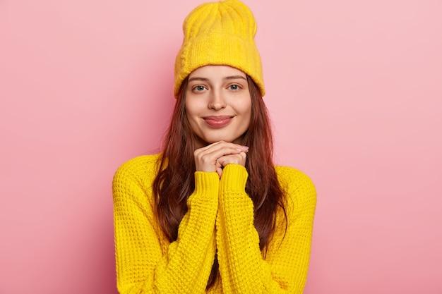 Aangenaam uitziende jonge donkerharige blanke vrouw heeft een tedere glimlach op het gezicht, houdt de handen onder de kin, heeft blauwe ogen, draagt een stijlvolle gele hoed en gebreide trui, modellen over de roze studiomuur