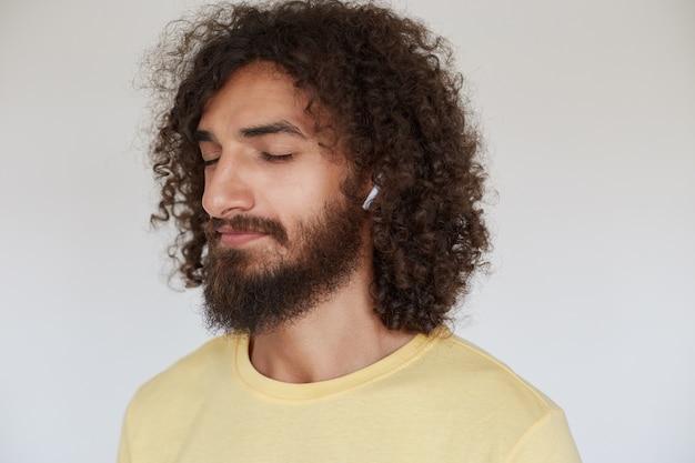 Aangenaam uitziende jonge donkerharige krullende man met weelderige baard die oortelefoons in geel t-shirt draagt, genietend van muziektrack en ogen gesloten houdt