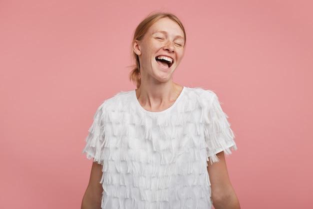 Aangenaam uitziende jonge gelukkig roodharige vrouw met paardenstaart kapsel die haar ogen gesloten houdt terwijl ze vreugdevol lacht, in een hoge geest is terwijl ze over roze achtergrond staat