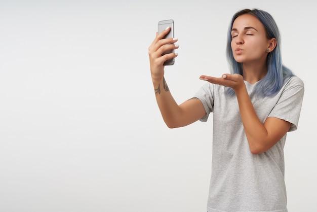 Aangenaam uitziende jonge getatoeëerde dame met kort blauw haar die haar ogen gesloten houdt terwijl ze luchtkus van haar smartphone blaast, geïsoleerd op wit