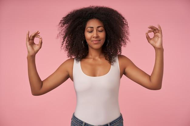 Aangenaam uitziende jonge krullende vrouw met donkere huid die de ogen gesloten houdt tijdens het mediteren, poseren op roze met zachte glimlach en handen opsteken in mudra-teken