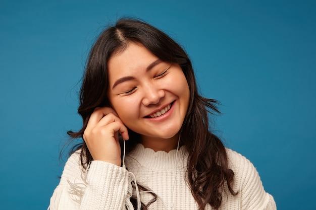Aangenaam uitziende jonge mooie aziatische dame met romantisch kapsel vrolijk lachend