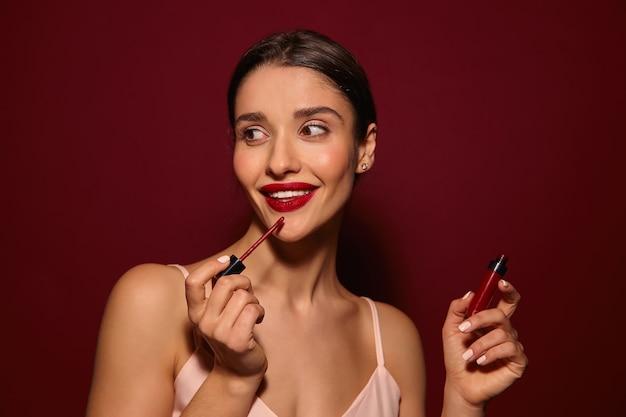 Aangenaam uitziende jonge mooie blije langharige brunette dame met rode lippen