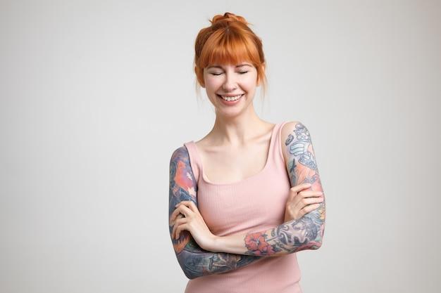 Aangenaam uitziende jonge mooie getatoeëerde vrouw die in een leuke bui is en gelukkig lacht met gesloten ogen, handen gekruist houden terwijl poseren op witte achtergrond