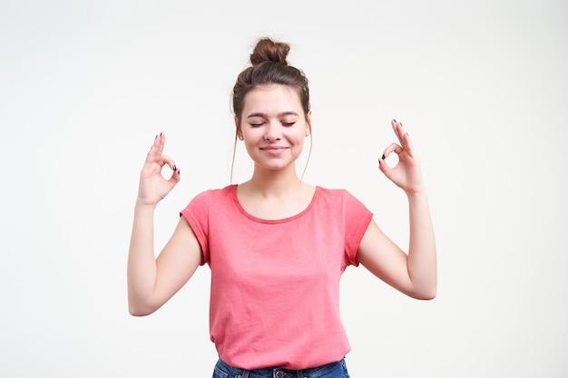 Aangenaam uitziende jonge positieve bruinharige dame die haar handen gesloten houdt tijdens het mediteren en handen opheft met mudra-gebaar, staande op witte achtergrond
