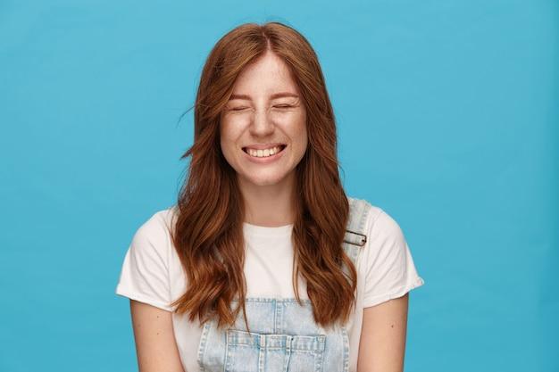 Aangenaam uitziende jonge roodharige blije vrouw die haar ogen gesloten houdt terwijl ze vrolijk lacht, in een hoge geest is terwijl ze in vrijetijdskleding over een blauwe achtergrond staat