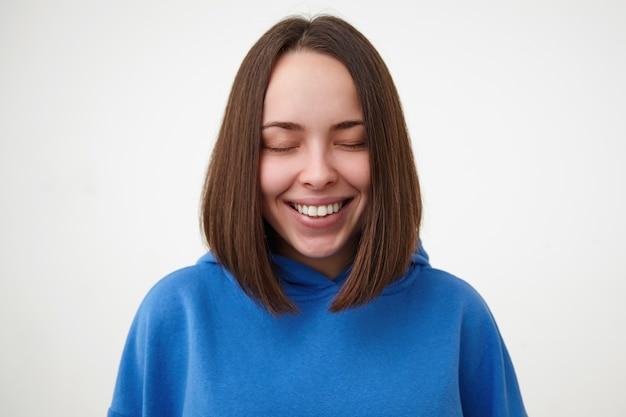Aangenaam uitziende jonge vrolijke bruinharige vrouw met bobkapsel die haar ogen gesloten houdt terwijl ze vrolijk lacht, gekleed in sportieve kleding terwijl ze zich voordeed op een witte muur
