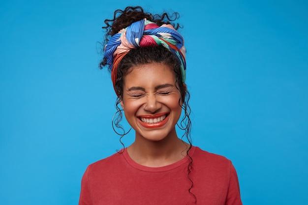 Aangenaam uitziende jonge vrolijke donkerharige dame met krullen die haar ogen gesloten houden terwijl ze vrolijk lacht, poseren over blauwe muur in casual t-shirt
