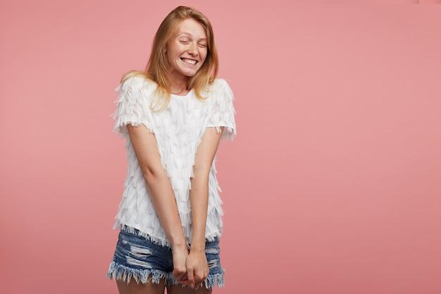 Aangenaam uitziende jonge vrolijke roodharige dame gekleed in wit feestelijk t-shirt en spijkerbroek korte broek handen naar beneden houden terwijl poseren op roze achtergrond, gelukkig lachend met gesloten ogen