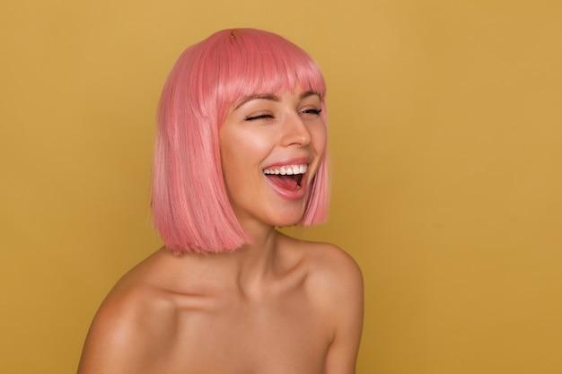 Aangenaam uitziende jonge vrolijke rozeharige vrouw die haar ogen gesloten houdt terwijl ze vreugdevol lacht, staande over de mosterdachtergrond met blote schouders