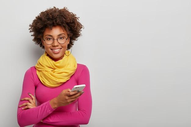 Aangenaam uitziende krullende vrouw gebruikt mobiele telefoon om online te chatten, glimlacht toothy, draagt een ronde bril