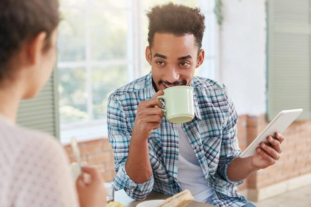 Aangenaam uitziende man met een specifiek uiterlijk drinkt koffie met cake, praat met zijn vrouw,