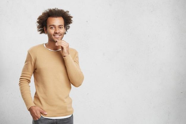 Aangenaam uitziende man van gemengd ras met trendy kapsel, nonchalant gekleed, houdt de hand op de kin