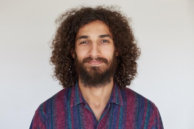 Aangenaam uitziende positieve brunette krullende man met weelderige baard die zachtjes glimlacht, een gestreept veelkleurig shirt draagt, in een goede bui is
