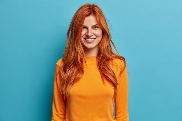 Aangenaam uitziende roodharige vrouw met sproeten glimlach, breed gekleed in trui met lange mouwen, heeft een vrolijke bui.