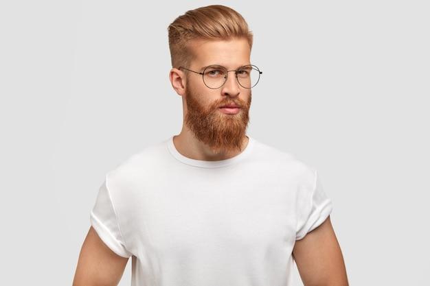 Aangenaam uitziende serieuze man staat in profiel, heeft een zelfverzekerde uitdrukking, draagt een casual wit t-shirt