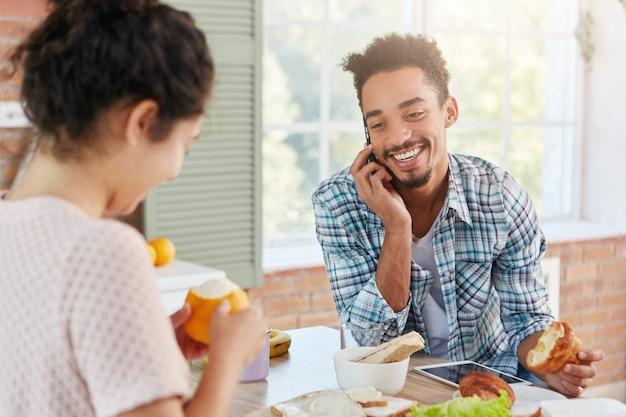 Aangenaam uitziende stijlvolle bebaarde man spreekt via slimme telefoon