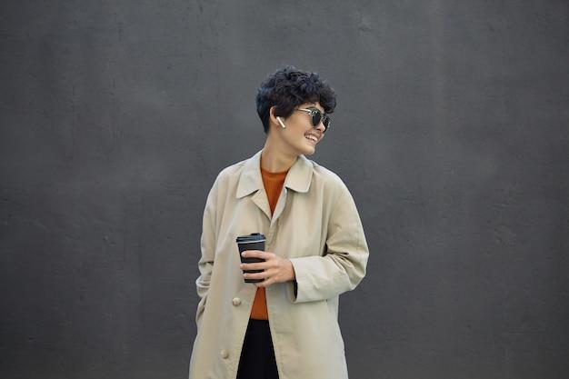 Aangenaam uitziende vrolijke jonge donkerharige vrouw met kort kapsel, zwarte papieren beker in opgeheven hand houden tijdens het lopen over stedelijke betonnen muur, trendy outfit dragen