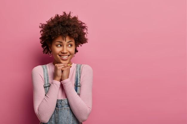 Aangenaam uitziende vrouw houdt de handen onder de kin, kijkt weg, heeft een tedere glimlach, draagt vrijetijdskleding, denkt aan iets goeds, poseert tegen een roze pastelkleurige muur, lege ruimte voor uw promotietekst