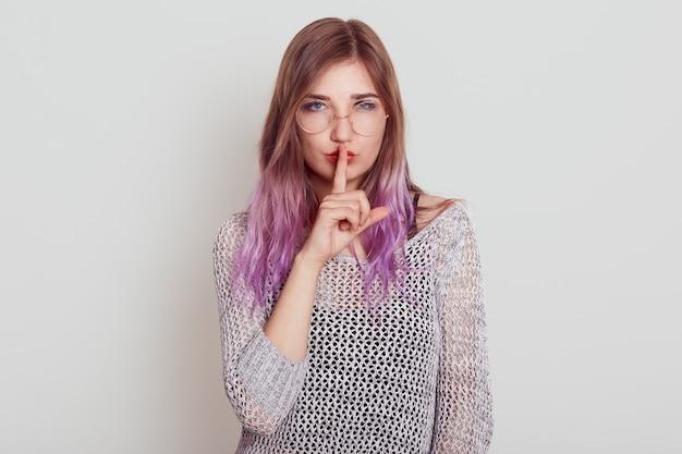 Aangenaam uitziende vrouw in grijs overhemd die naar voren kijkt met de vinger in de buurt van de lippen, haar gebaar toont en vraagt om te zwijgen
