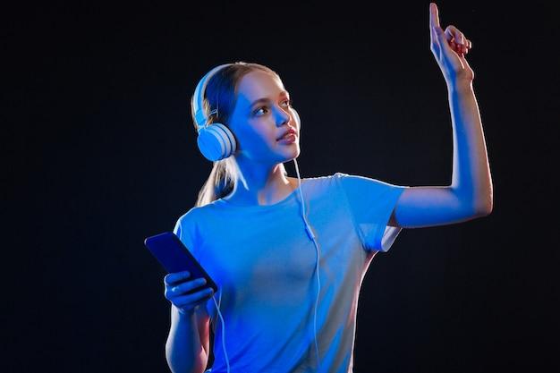 Aangenaam vermaak. leuke jonge vrouw die naar haar vinger kijkt tijdens het luisteren naar muziek