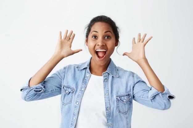 Aangenaam verrast afro-amerikaanse vrouw die met afgeluisterde ogen kijkt en haar handen omhoog houdt, haar mond open van verbazing opent en niet verwacht zo'n groot cadeau te ontvangen. gelukkig donkere huid model geïsoleerde ov