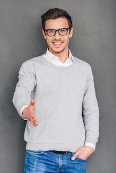 Aangenaam! vrolijke jonge man die zijn hand uitstrekt ter begroeting