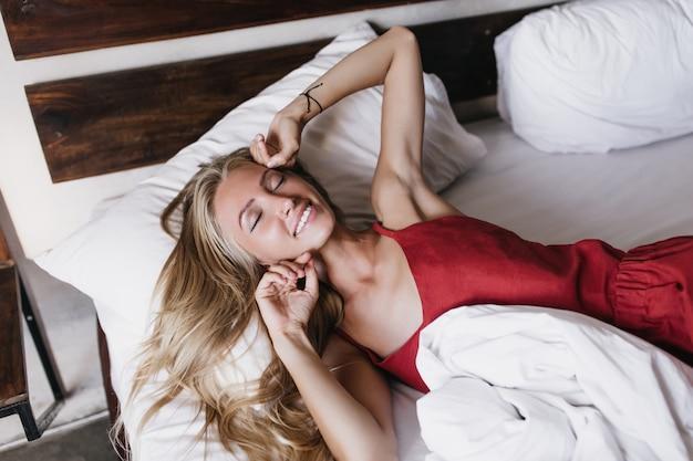 Aangenaam vrouwelijk model in rode pyjama die in het weekend slaapt. aanbiddelijke blonde vrouw die op blad met glimlach ligt.