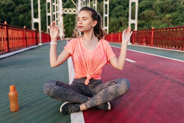 Aangenaam wit vrouwelijk model dat na een zware training ontspant. buiten schot van charmante vrouw in zwarte sneakers doet yoga in het stadion.