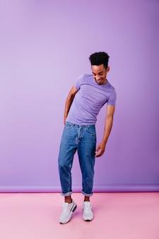 Aangename afrikaanse man in witte schoenen naar beneden te kijken met een glimlach. binnenfoto van goedgehumeurd mannelijk model met krullend kapsel.