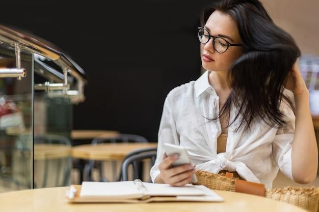 Aangename aziatische zakenvrouw die aan het chatten is, gebruikt een smartphone die aantekeningen maakt in kladblok aan tafel in café