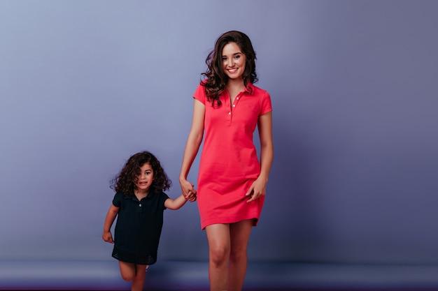Aangename blanke vrouw hand in hand met krullend klein kind. portret van mooie moeder en charmante dochter geïsoleerd op paarse muur.