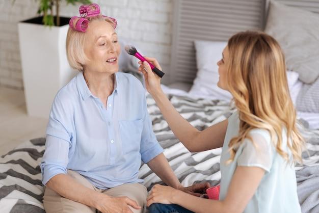 Aangename blonde vrouw die op het punt staat wat make-up op het gezicht van haar moeder aan te brengen terwijl ze roze haarrollers draagt en naar de borstel kijkt