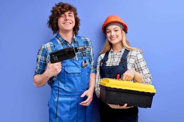 Aangename constructeurs met instrumentenhulpmiddelen poseren geïsoleerd op blauwe achtergrond
