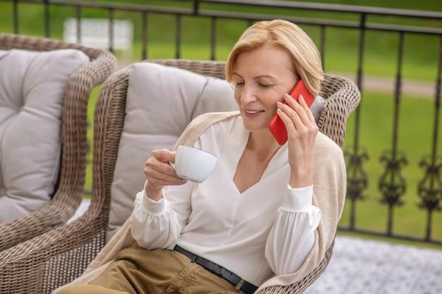 Aangename dame zittend in de leunstoel bellend op haar smartphone