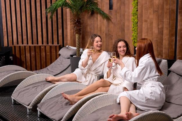 Aangename dames genieten van het drinken van champagne in de spa drie mooie vrouwen die badjassen dragen met een koele rustvakantie